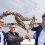 Geert Takke (Infra Composites) gedeputeerde Michiel Schrier en Eric Poel (Reef) houden het vlas omhoog waarvan de brug misschien gemaakt wordt.